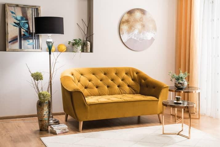 Żółta welurowa sofa pikowana Galaxy na drewnianych nóżkach.